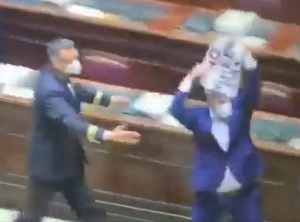 """<p>An Italian MP holding a """"no green pass"""" sign was chased out of parliament by security during a protest against Italy's vaccine passport scheme</p>"""