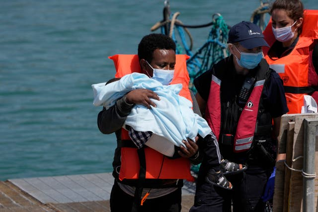 <p>A man and a child are disembarked from a British border force vessel in Dover</p>