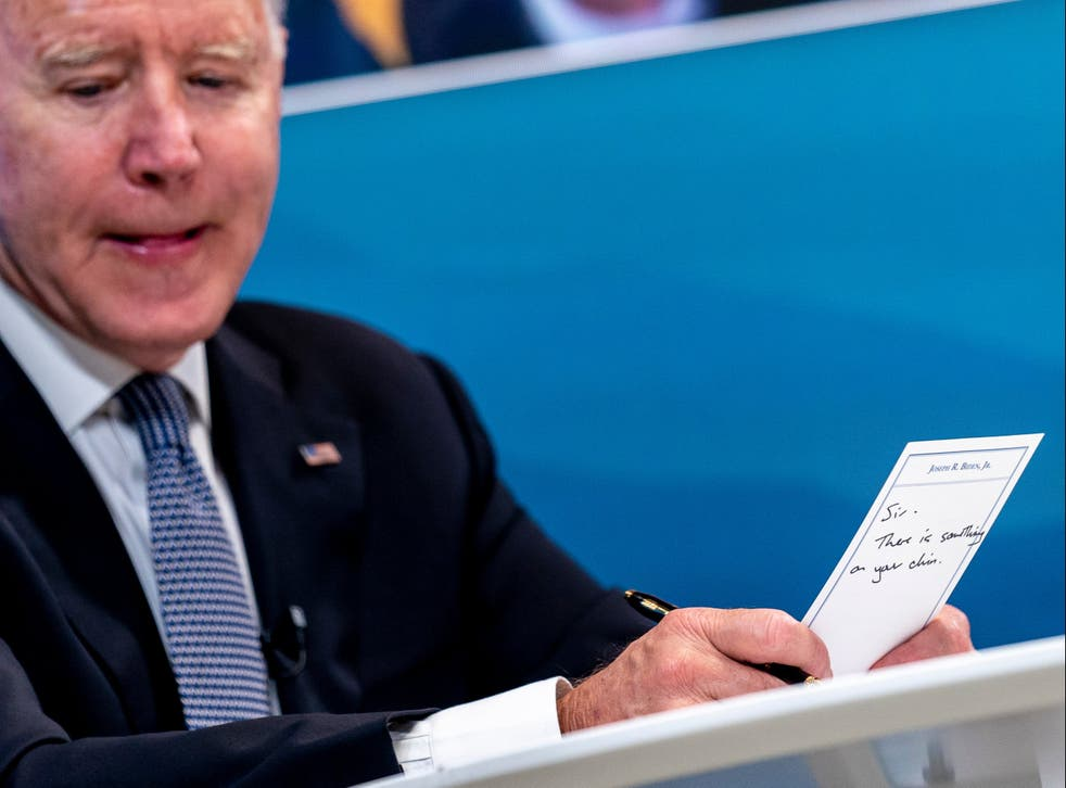 """<p>President Joe Biden holds a card handed to him by an aide that reads """"Sir, there is something on your chin""""</p>"""