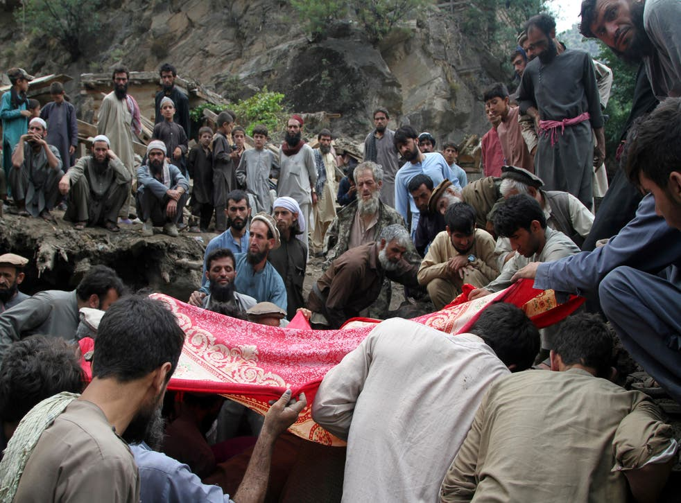 <p>Locals search for victims of a mudslide following heavy flooding in Nuristan</p>