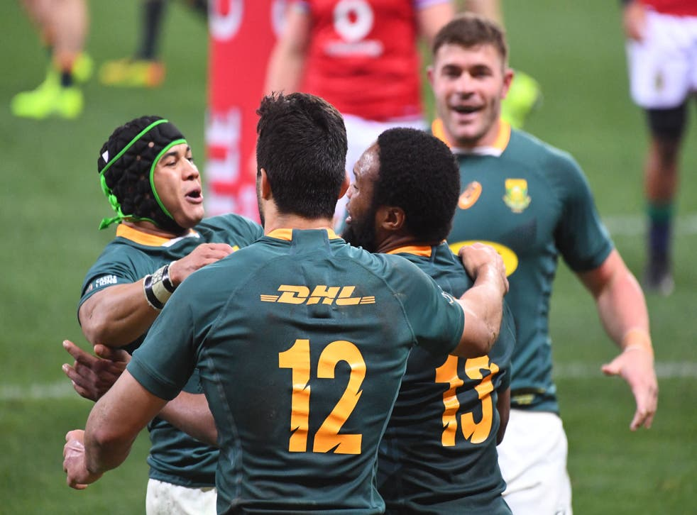 <p>South Africa's center Lukhanyo Am (R) is celebrated by teammates</p>