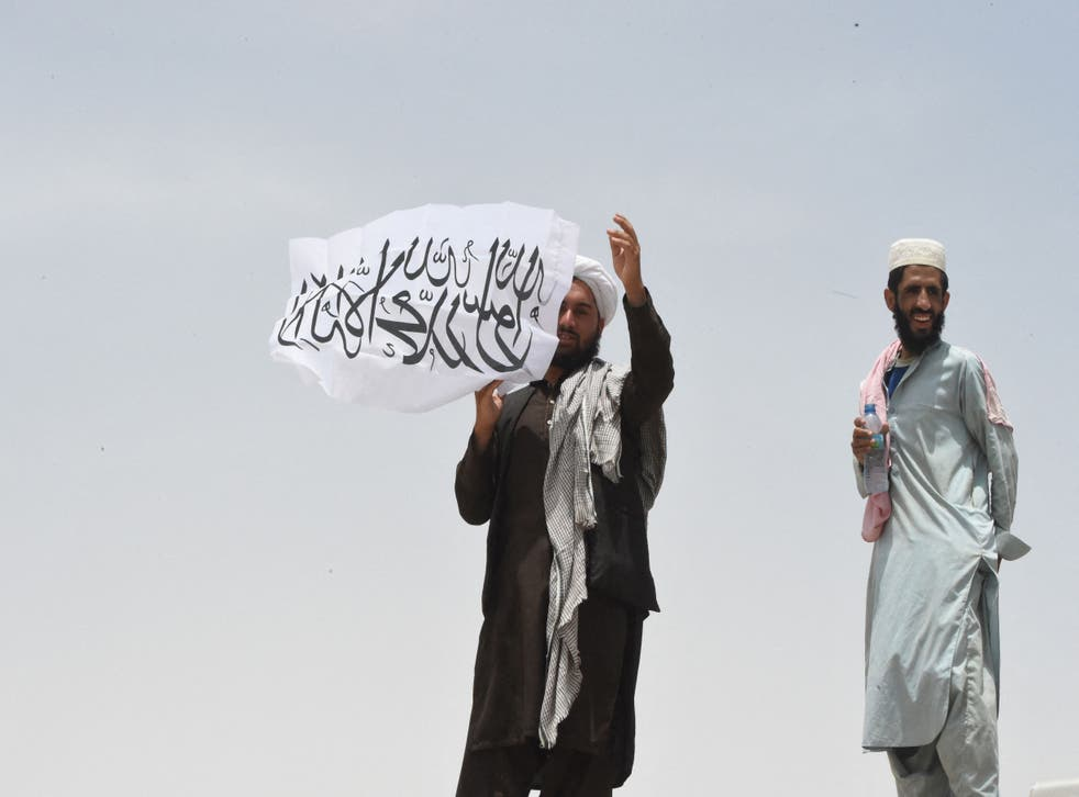 <p> A man standing on the Afghan side of the border holds a Taliban flag near a crossing point in Pakistan</p>