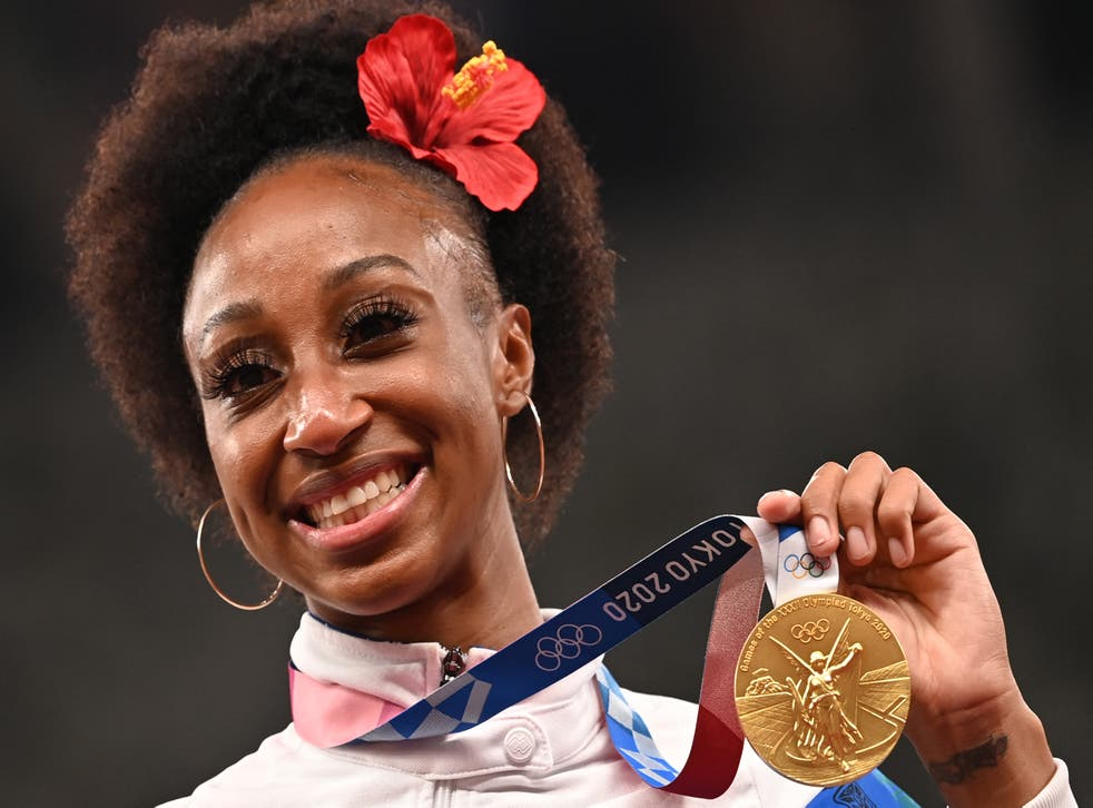 <p>Gold medalist Puerto Rico's Jasmine Camacho-Quinn poses on the podium for the women's 100m hurdles final during the Tokyo 2020 Olympic Games at the Olympic Stadium in Tokyo on August 2, 2021</p>