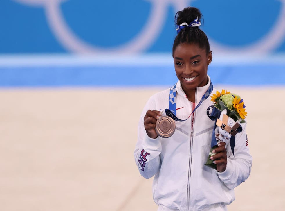<p>Simone Biles poses with her bronze medal, won in the beam final at Tokyo 2020 on 3 August</p>