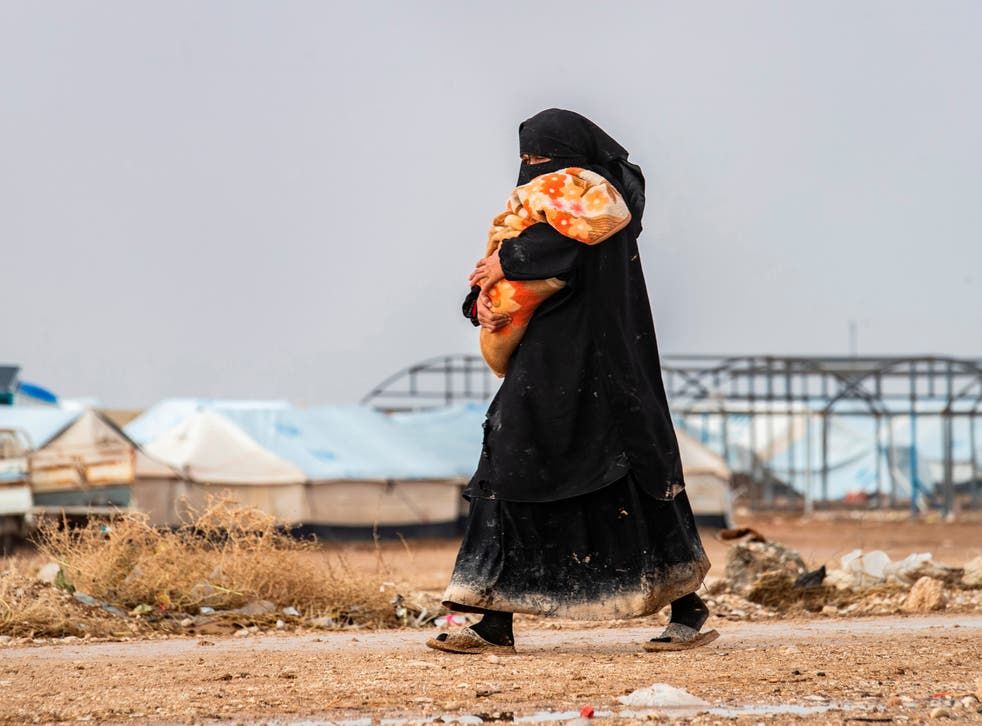 <p>A woman carrying a toddler walks at the Kurdish-run al-Hol camp for the displaced where families of Islamic State (IS) foreign fighters are held, in the al-Hasakeh governorate in northeastern Syria on 9 December 2019</p>