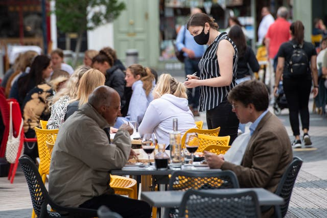 File photo dated 29/06/21 of a waitress wearing a face covering serving diners at outside tables in Kensington, London.