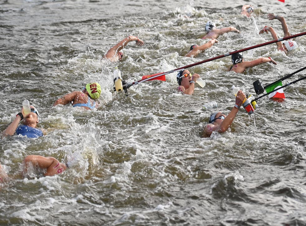<p>Competitors take refreshments at a feed station in the women's 10km marathon swimming event during the Tokyo 2020 Olympic Games at the Odaiba Marine Park in Tokyo on August 4, 2021.</p>