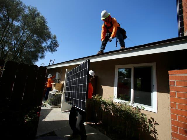 Los trabajadores levantan un panel solar sobre un techo durante una instalación solar residencial en Scripps Ranch, San Diego, California, EE. UU. 14 de octubre de 2016