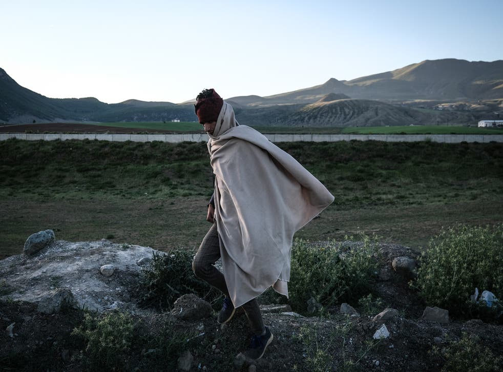 <p>A young Afghan man walks next to a railway as they come from Van city after crossing the Iran-Turkey border </p>