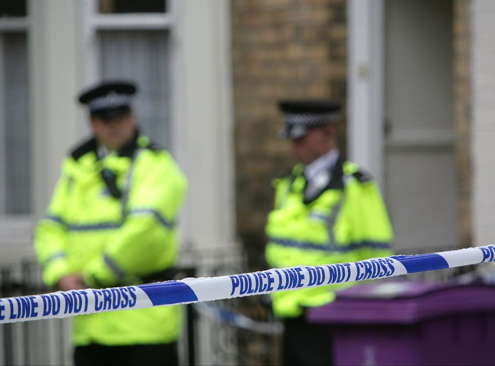 <p>Police officers stand outside a house in Hatherley Street, Liverpool after a raid searching for terror suspects in July 2007</p>