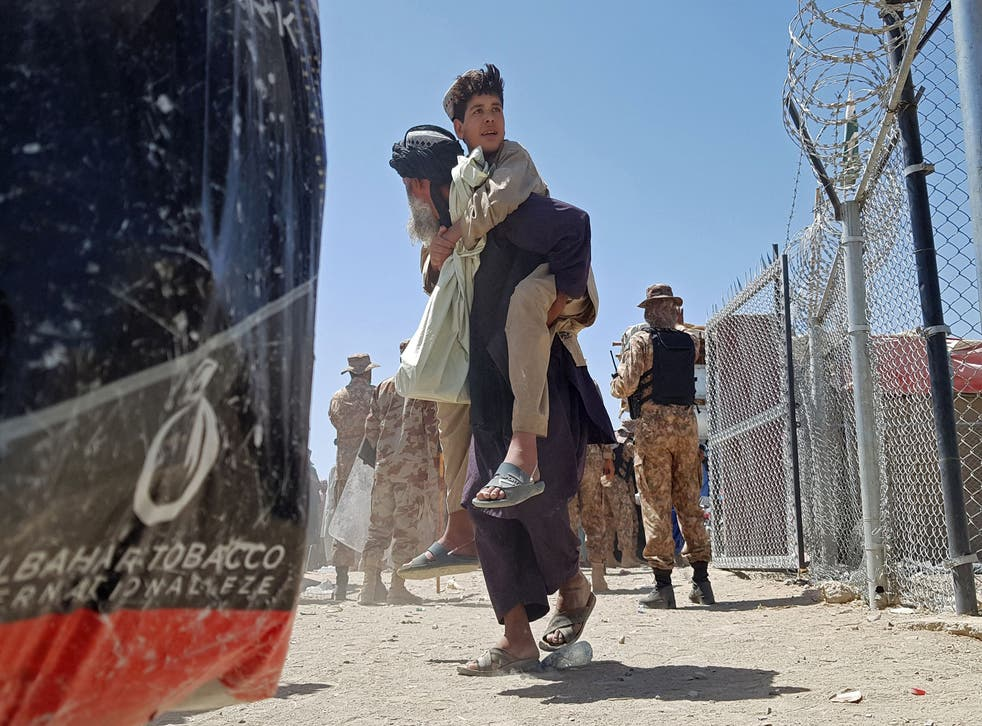 <p>A stranded Afghan carries his son at the Pakistan-Afghanistan border crossing point in Chaman</p>