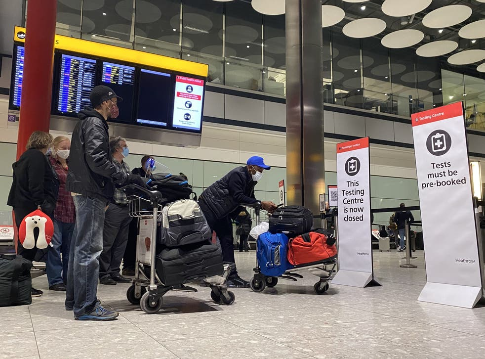 <p>This file photo from 18 August shows passengers waiting in line outside the testing centre in London Heathrow Airport's Terminal 5</p>