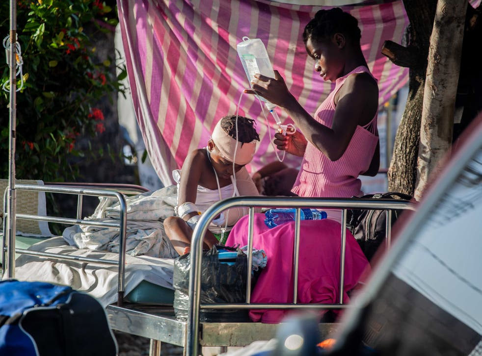 <p>A boy is tended to outside Les Cayes General Hospital after a 7.2-magnitude earthquake on 15 August 2021 in Les Cayes, Haiti</p>