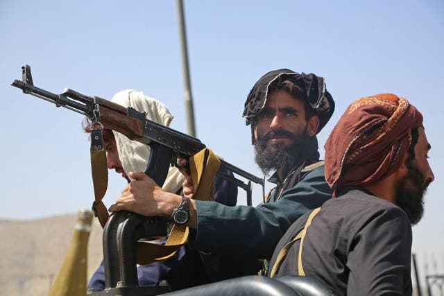 <p>Taliban fighters stand guard in a vehicle along the roadside in Kabul on 16 August</p>
