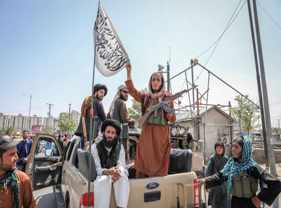 <p>Taliban fighters are seen on the back of a vehicle in Kabul, Afghanistan</p>