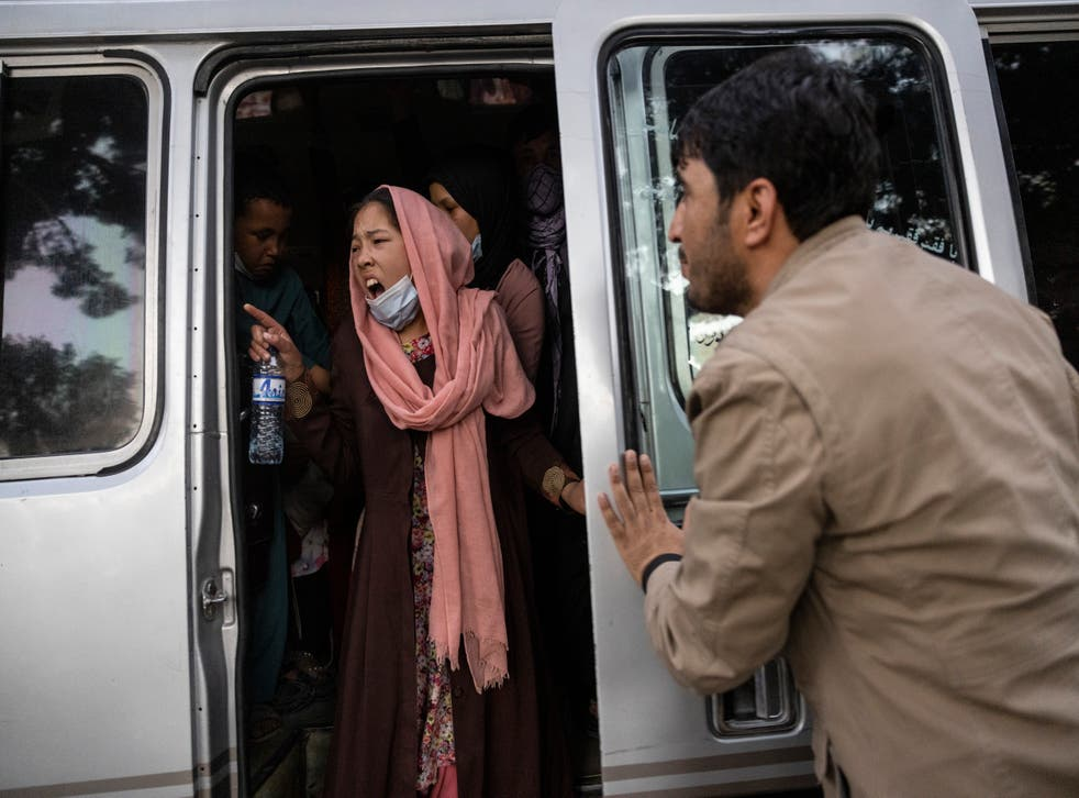 <p>Woman urges her family to hurry up as displaced Afghans from northern part of country are evacuated from camp to Kabul</p>