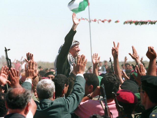 <p>PLO chairman Yasser Arafat waves to a crowd of cheering Palestinians after he crossed the Rafah border point on 1 July 1994, entering the newly self-ruled Gaza Strip for the first time in 27 years</p>