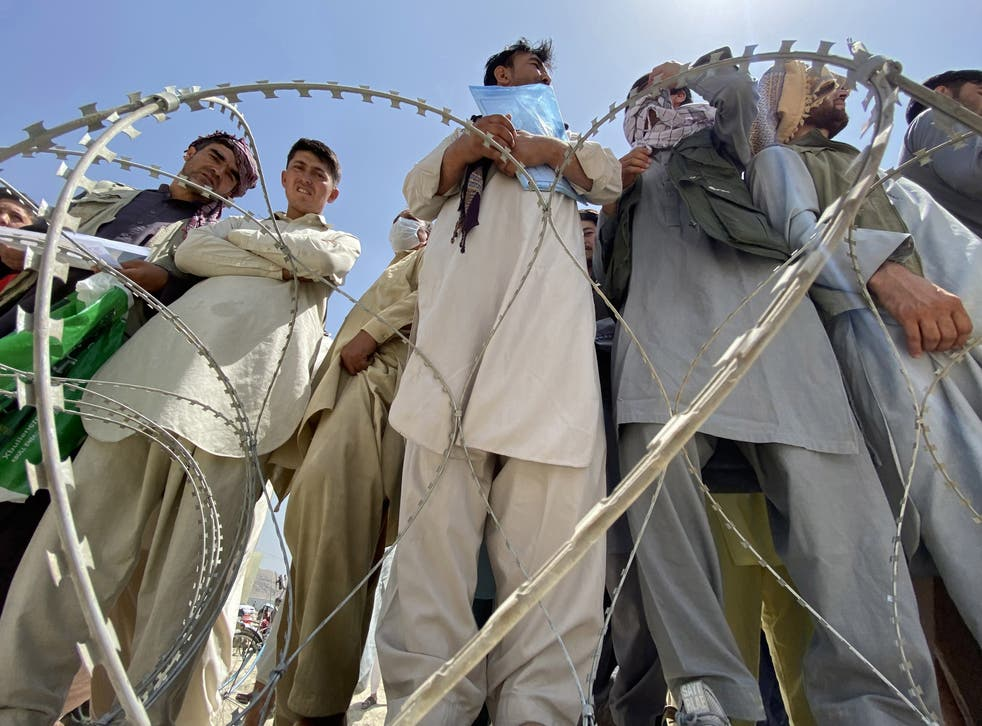 <p>Afghans including those who worked for the US, Nato, the European Union and the United Nations in Afghanistan wait outside the Hamid Karzai International Airport to flee the country</p>