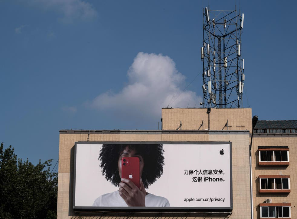 <p>A cellphone tower on top of a building is seen next to a commercial billboard for the iPhone in Beijing</p>