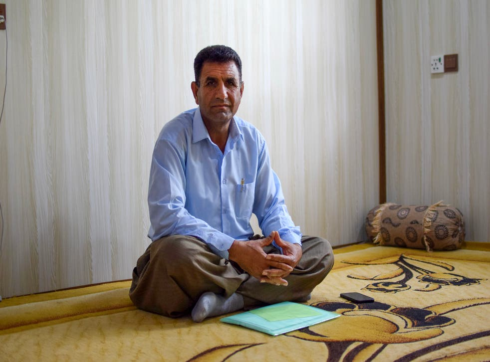 <p>Iranian Kurdish refugee Husein Karimi sits with a folder of precious documents in his living room in the Barika refugee camp in the Kurdistan Region of Iraq in April 2021</p>