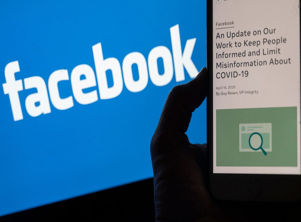 <p>Smart phone screen displays a new policy on Covid-19 misinformation with a Facebook website in the background</p>