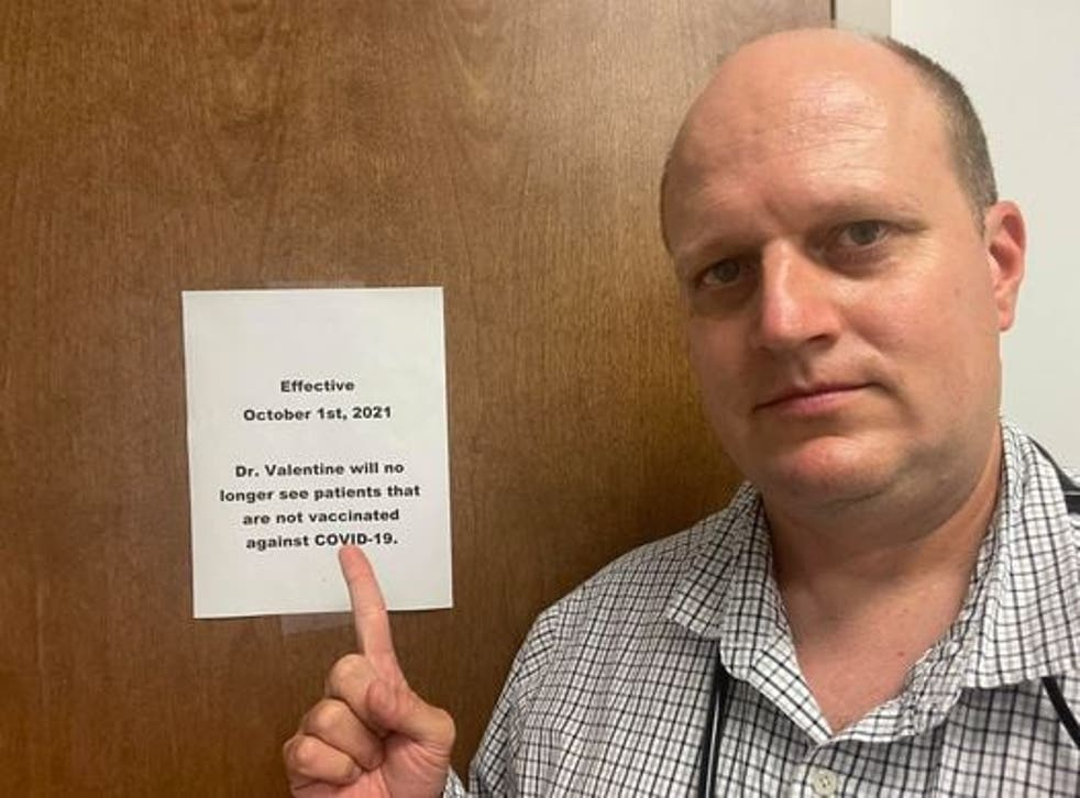 <p>Dr Jason Valentine points to his sign requiring patients to be vaccinated. </p>