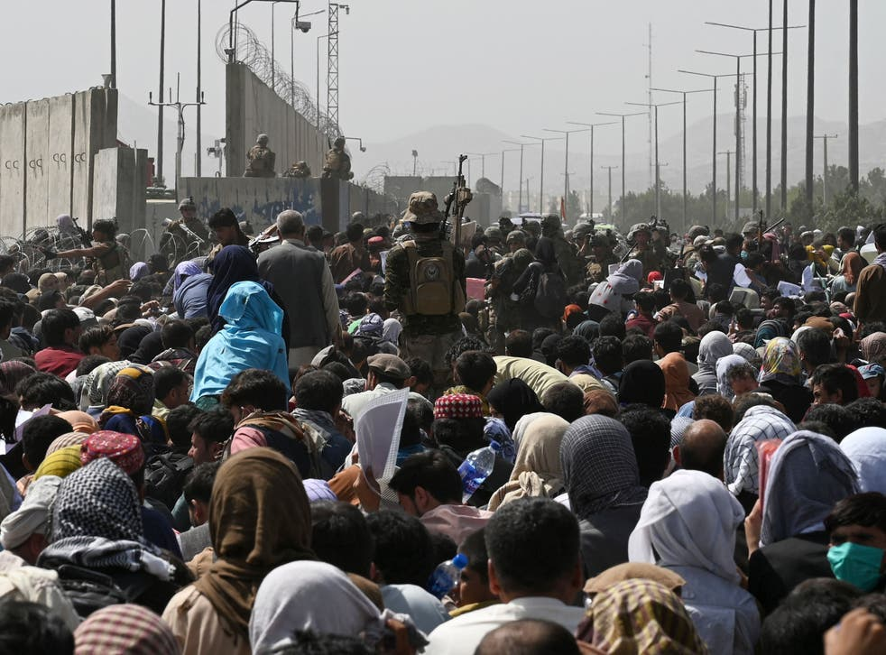 <p>Afghans gather on a roadside near the military part of the airport in Kabul in a desperate bid to leave the country </p>
