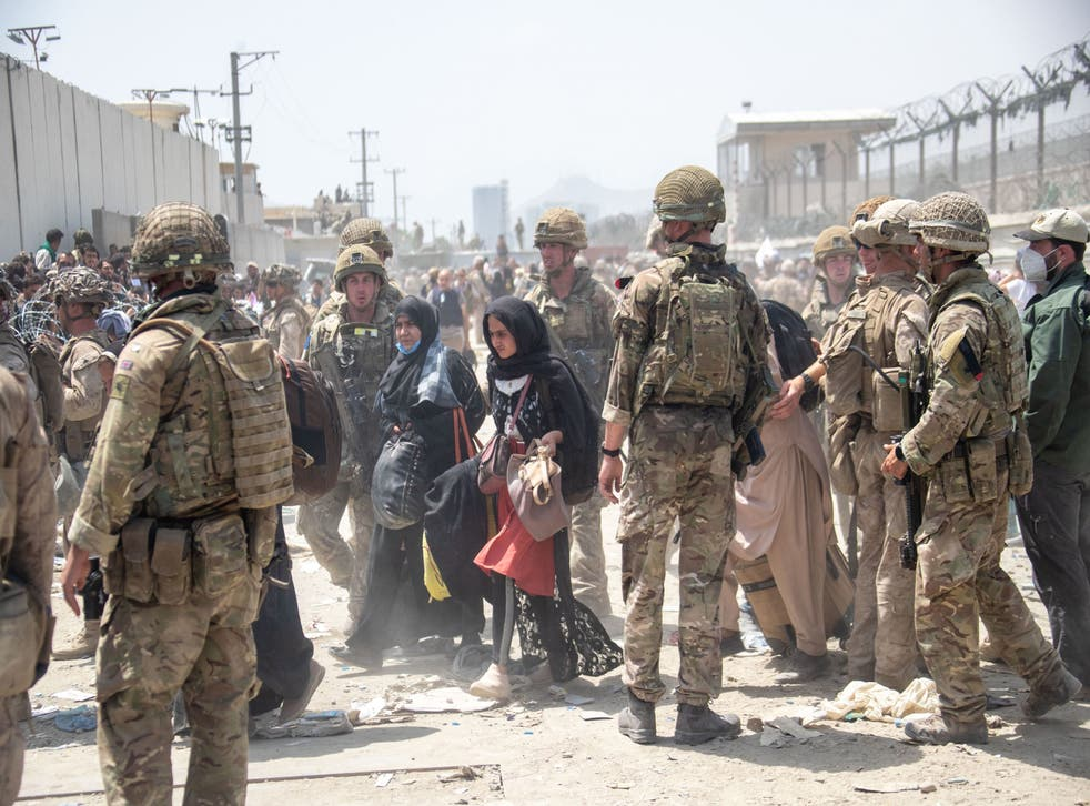 <p>Members of the British and American military help evacuate of people out of Kabul</p>