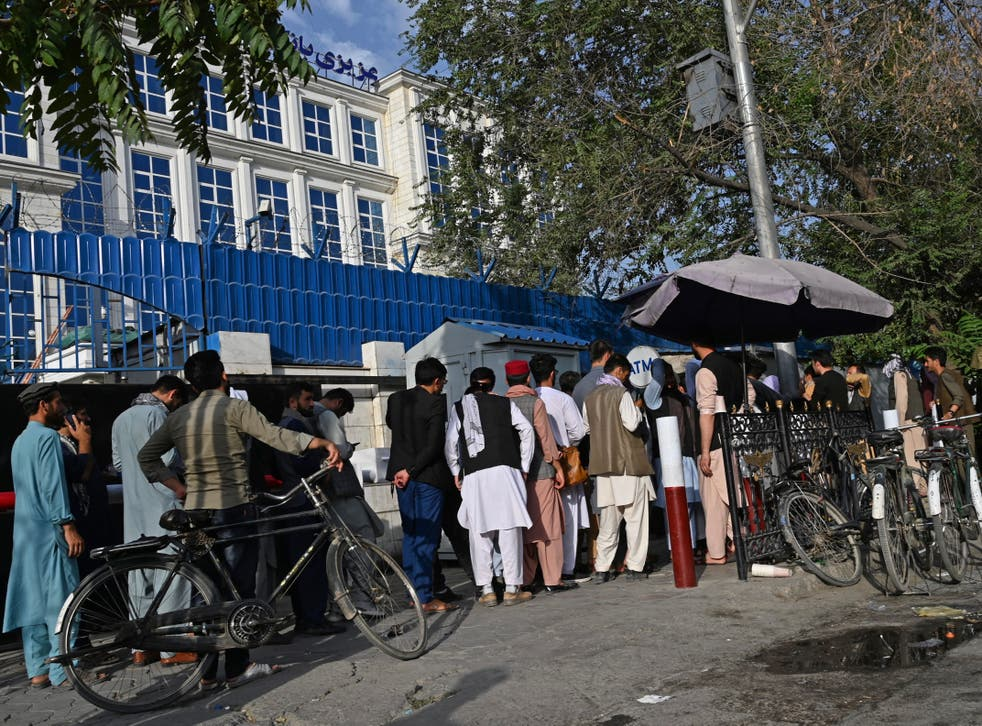 <p>Afghans queue to collect money from an ATM in front of a bank in Kabul after the Taliban takeover</p>