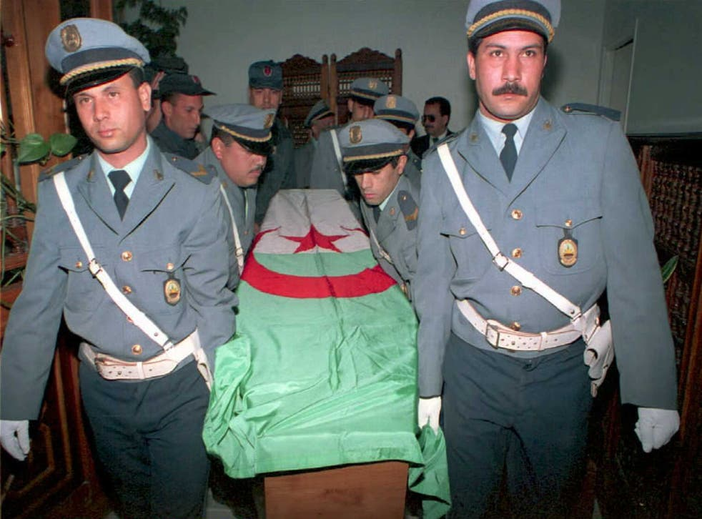 <p>Police carry the coffin of Rachida Hammadi, a television reporter, flown back to Algiers for burial. She died after an    attack by Islamic extremists</p>