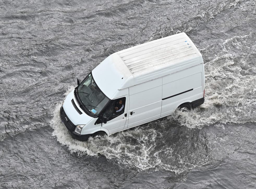 <p>A van drives through water on a flooded road in London</p>