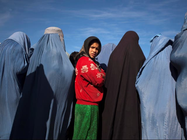 <p>An Afghan girl stands among widows during a project by CARE International in Kabul earlier this year</p>