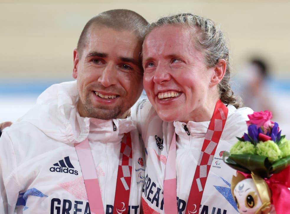 <p>Gold medalists Neil and Lora Fachie celebrate at the Izu Velodrome</p>