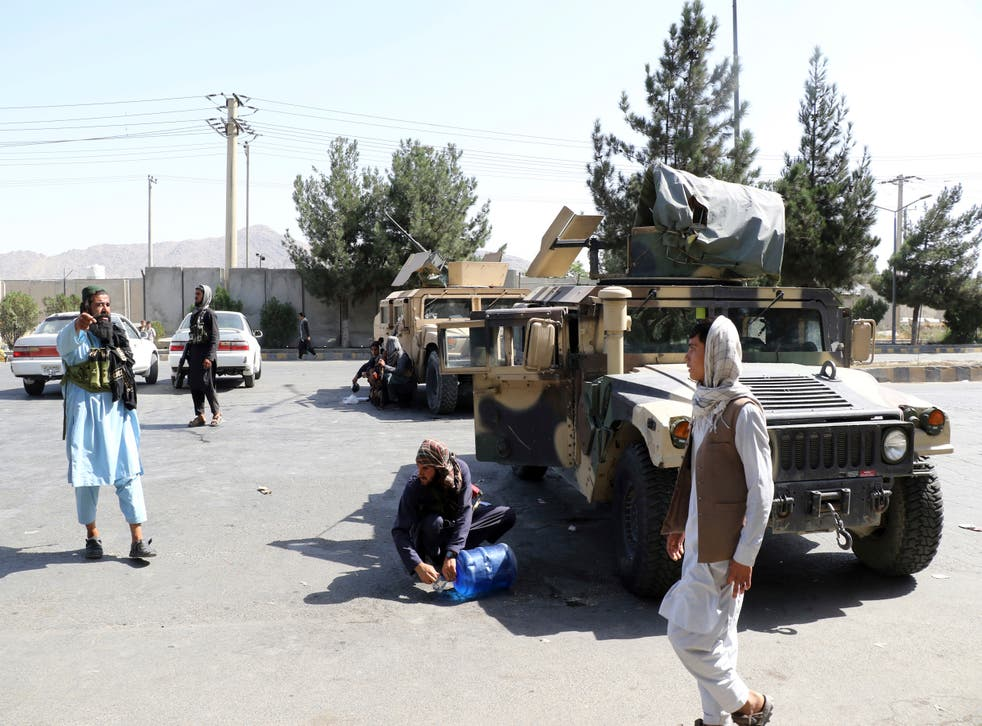 <p>Taliban fighters stand guard outside Kabul airport</p>
