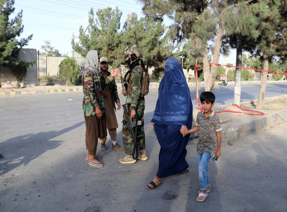 <p>Taliban fighters stand guard at a checkpoint near the gate of Hamid Karzai international Airport in Kabul, Afghanistan</p>