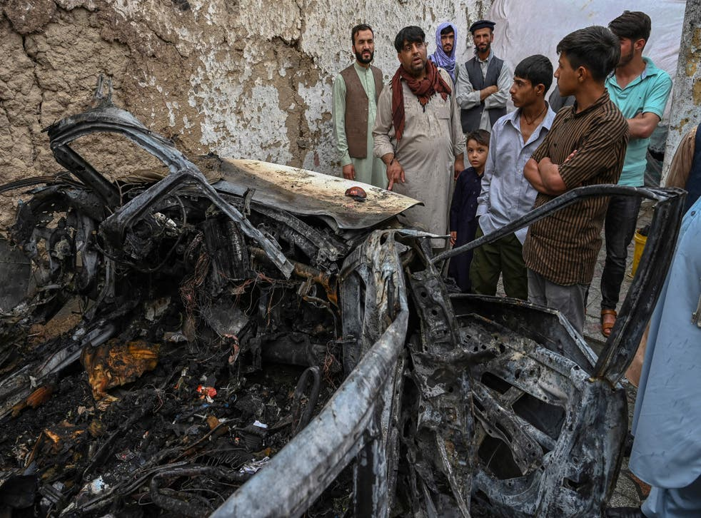 <p>Afghan residents and family members of the victims gather next to a damaged vehicle inside a house, day after a US drone airstrike in Kabul on 30 August, 2021. </p>
