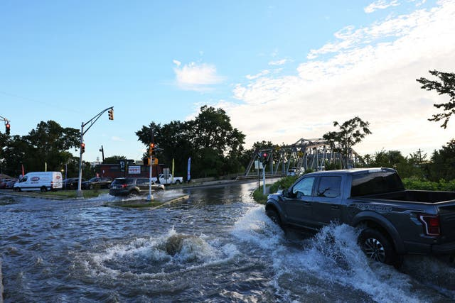 <p>Vehicles drive through flooded River Drive as water gushes out of a manhole on 2nd September in Passaic City. Governor Phil Murphy declared a state of emergency as Tropical Storm Ida caused flooding and power outages throughout New Jersey </p>