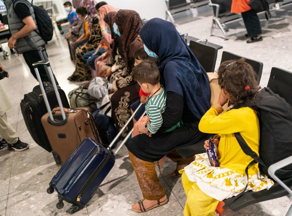 <p>Refugees from Afghanistan wait to be processed after arriving on a evacuation flight at Heathrow Airport</p>