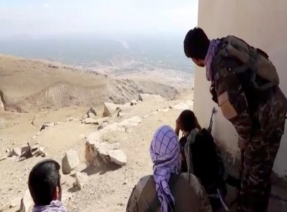 <p>Members of National Resistance Front observe by a house near Panjshir Valley</p>