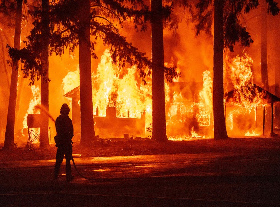 <p>File: A firefighter sprays water on a propane tank as a home burns due to the Dixie fire in the Indian Falls neighborhood of unincorporated Plumas County, California</p>