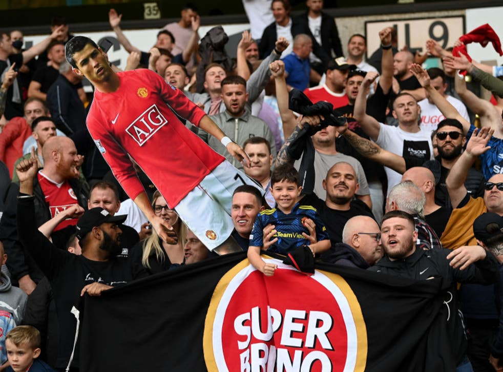 <p>Manchester United fans hold up a cardboard cutout of Cristiano Ronaldo</p>