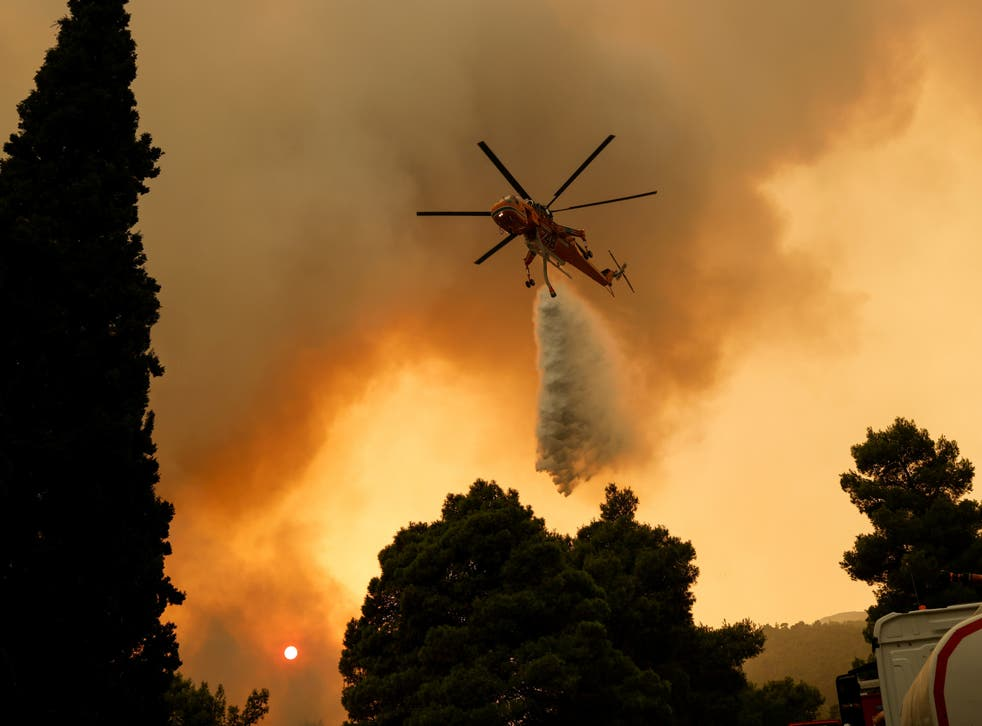 <p>A firefighting helicopter makes a water drop as a wildfire burns in the village of Vilia, near Athens </p>