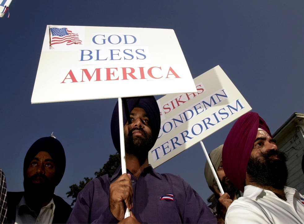<p>Sikh men carry patriotic placards at a community service to remember victims of terrorist attacks on  10 October, 2001 in Santa Ana</p>