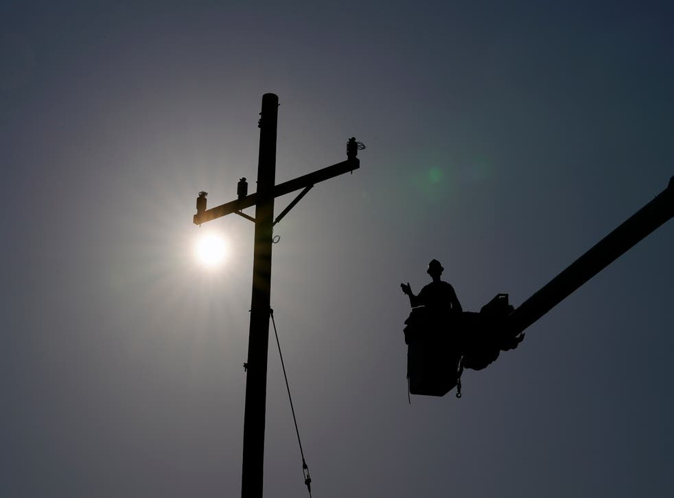 <p>In the aftermath of Hurricane Ida, a lineman gestures as he works on a power pole</p>