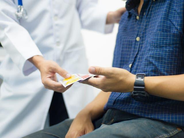 <p>A doctor hands a man a condom</p>