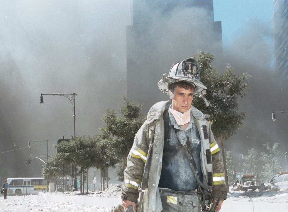 <p>An unidentified firefighter walks away from the rubble on 9/11 </p>