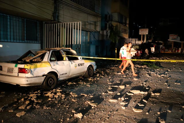 <p>Una pareja pasa junto a un taxi que resultó dañado por la caída de escombros después de un fuerte terremoto en Acapulco, Guerrero, el martes 7 de septiembre de 2021. El terremoto sacudió el sur de México cerca del complejo turístico, provocando que algunos edificios se balanceen en la Ciudad de México a 379 kilómetros de distancia.</p>