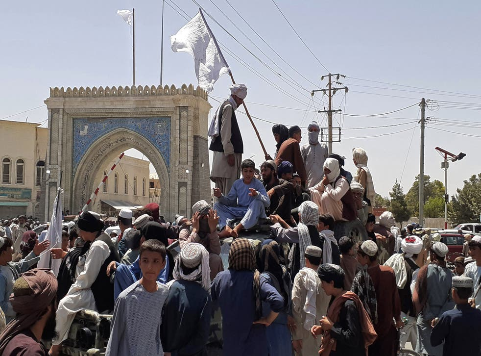 <p>File: Taliban fighters stand on a vehicle along the roadside in Kandahar on 13 August 2021</p>