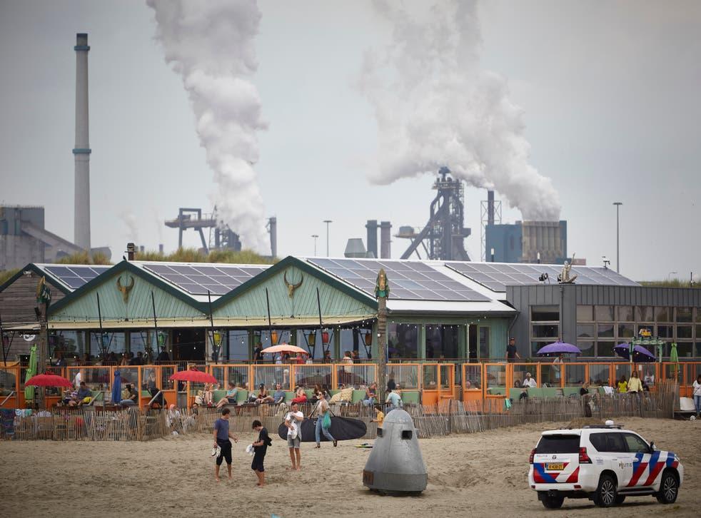 <p>People enjoy the beach near the Tata Steel plant in Velsen-Noord</p>