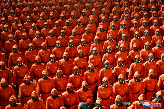 <p>North Korean troops wearing gas masks and bright red suits parade during a celebration of the nation's 73rd anniversary this week</p>